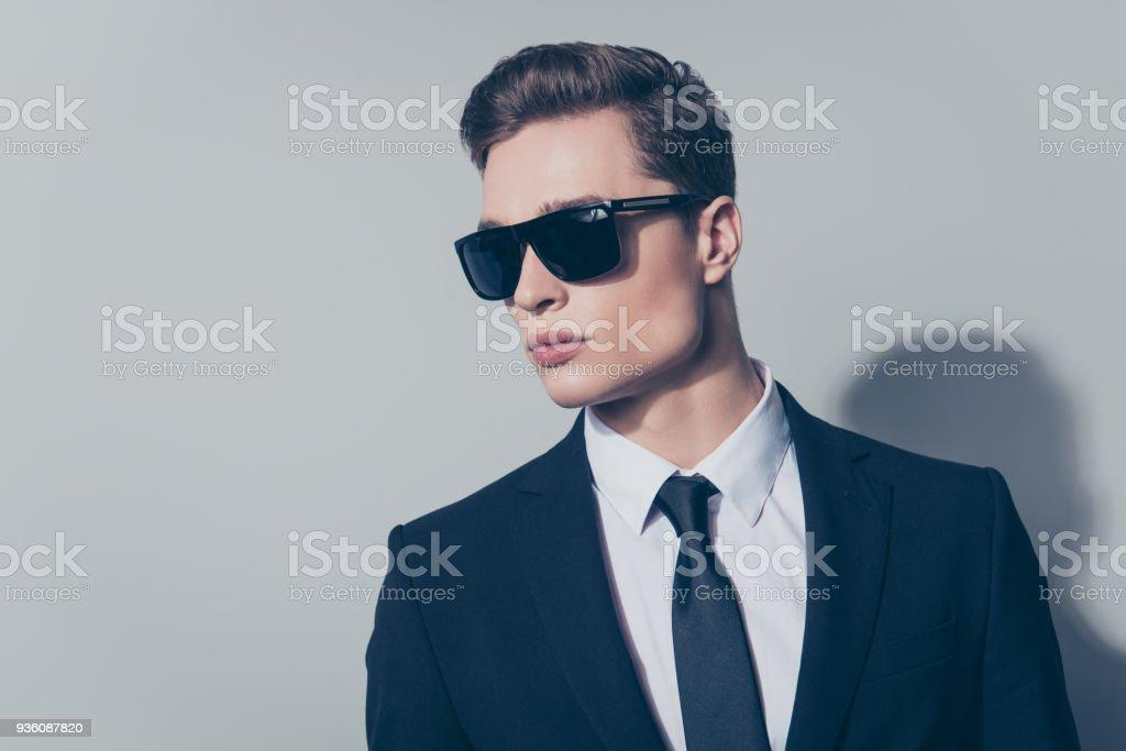 5ddcca18471b75 Porträt von stilvollen gut aussehende Mann im schwarzen Anzug und  Sonnenbrille auf grauem Hintergrund isoliert hautnah