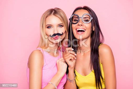 istock Close up portrait of two crazy funny cheerful comic attractive beautiful girlfriends wearing summer clothes and having fun using fake mustache and eyewear, isolated on bright pink background 932215460