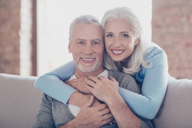 close up portrait of two happy old married people, they are hugging and have perfect shiny white smiles - dental implants stock photos and pictures