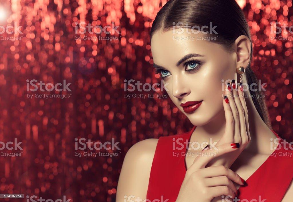 Feche o retrato da mulher em uma maquiagem elegante. Manicure em uma cores vermelho e preto. - foto de acervo