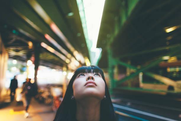 z bliska portret kobiety podczas loo0king się w mieście - selektywna głębia ostrości zdjęcia i obrazy z banku zdjęć