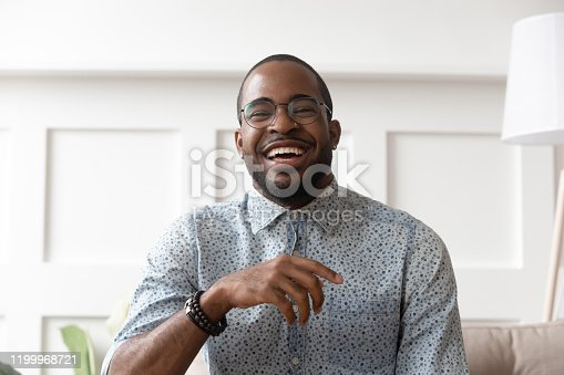 Close up head shot portrait of happy african american man in eyeglasses looking at camera, young smiling black male blogger influencer recording video, talking, laughing, having fun at home.
