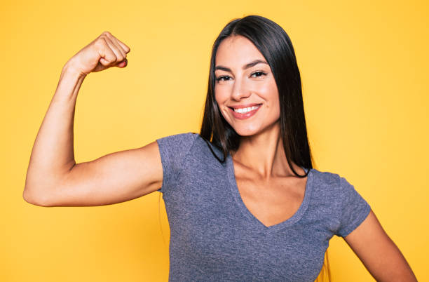 close up portrait of young cute sporty smiling brunette woman while she shows her arms and biceps on camera - muscolo foto e immagini stock