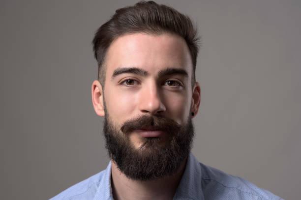 porträt des jungen eleganten bärtigen erwachsenen mann mit braunen haaren und augen blick in die kamera hautnah - braune augen stock-fotos und bilder