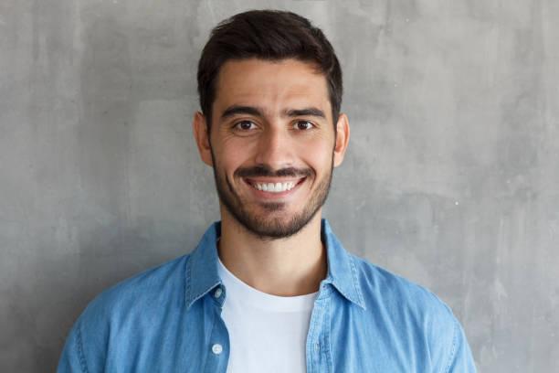 porträt des jungen glücklich lächelnde freundlicher mann nahaufnahme - zahnweiss stock-fotos und bilder