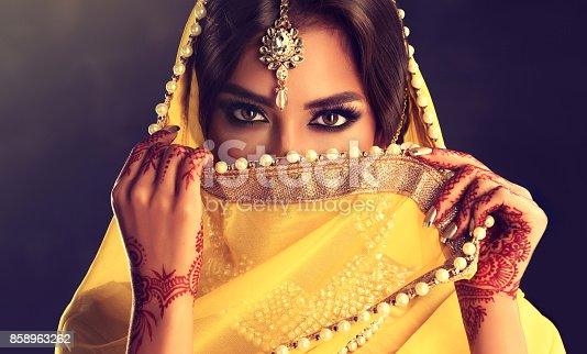 Close up portrait of young indian woman is covering part of the face by yellow cloth. Bright make up, long eyelashes and tender look. Henna tattoos(mehndi) and gilded manicure on hands.