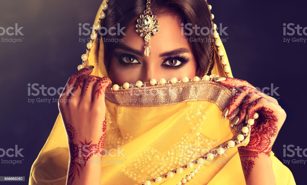 Close up portrait of young indian woman is covering part of the face by yellow cloth. stock photo