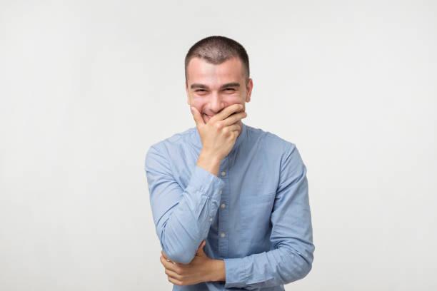 porträt des jungen menschen lachen und bedeckt den mund mit der hand über weißem hintergrund hautnah. - versuche nicht zu lachen stock-fotos und bilder