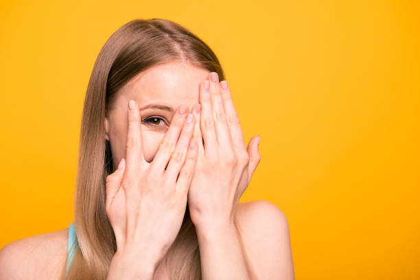 close up portrait of young model woman close her eyes with palms, peeking out open fingers isolated on bright yellow background with copy space for text - donna si nasconde foto e immagini stock