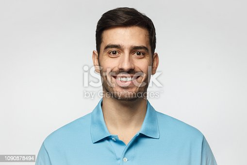 Close up portrait of young smiling handsome man in blue polo shirt isolated on gray background