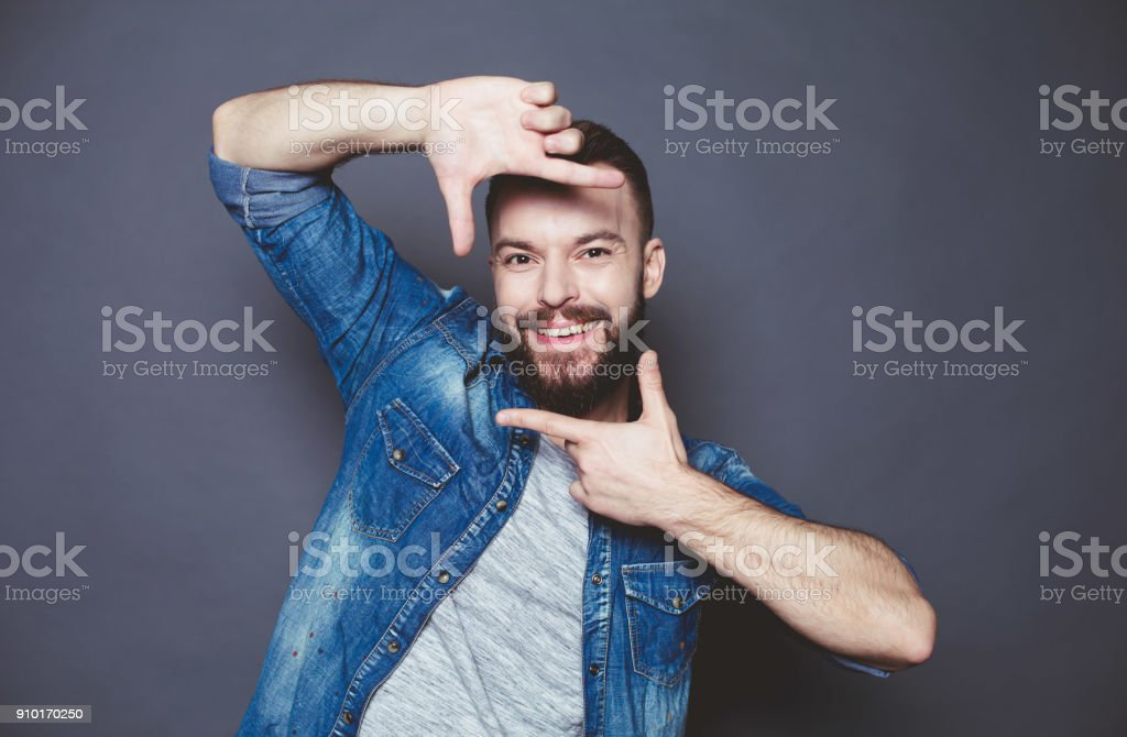 Close up portrait of Young stylish smiling guy in a denim jacket posing on a gray background. stock photo