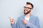 istock Close up portrait of young successful brunete bearded stock market broker guy on the pure light background, he is smiling, wearing suit and is pointing on a copyspace with his fingers 928020730