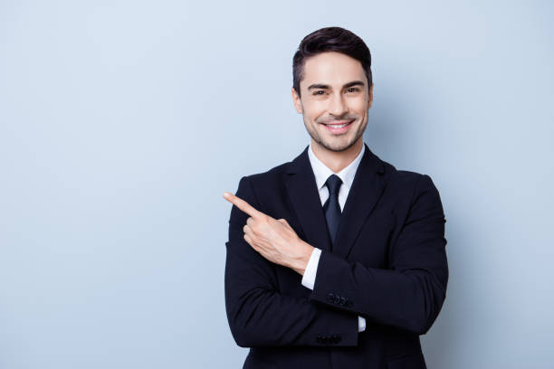 Close up portrait of young successful brunete  stock-market broker guy on the pure light blue background, he is smiling, wearing suit with tie and is pointing on a copyspace with his finger stock photo