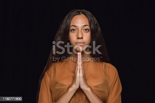 Close up portrait of young african-american woman isolated on black studio background. Photoshot of real emotions of female model. Facial expression, human nature. Praying and looks hopeful.