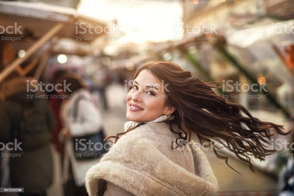 Close up portrait view of charming gorgeous stylish attractive beautiful young happy girl in sweater and jacket turning back and looking at the camera while standing in town sunny street while passersby walking around. stock photo