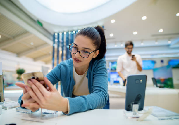 close up portrait view of cute excited charming young student girl with eyeglasses holding shiny new mobile while her boyfriend testing another behind her in a tech store. - happy person buy appliances stock photos and pictures