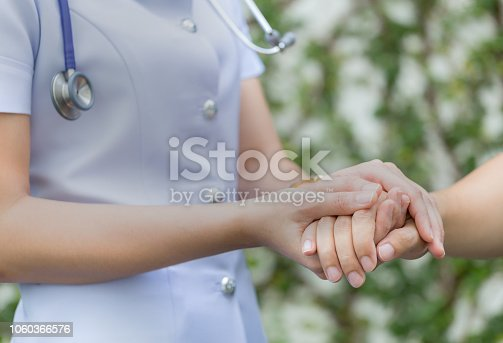 958891774istockphoto Close up portrait view of middle aged professional nurse holding hands with a patient. 1060366576