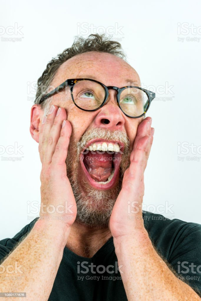 Close up portrait with white background of an adult male with grizzled beard and glasses shouting. stock photo