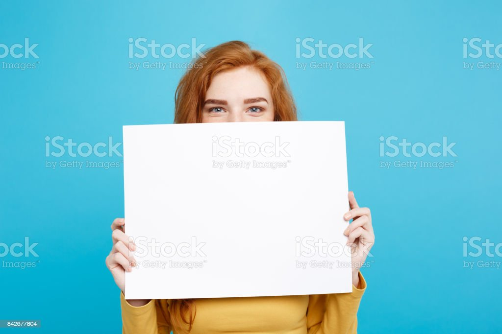 Close up Portrait young beautiful attractive redhair girl smiling showing blank sign. Blue Pastel Background. Copy space. stock photo