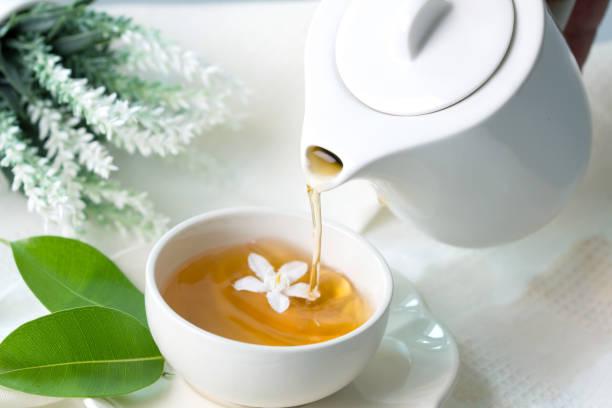Nahaufnahme Gießen heiße Jasmin-Tee in einer Tasse Weißer Tee, Tee-Zeremonie Konzept – Foto