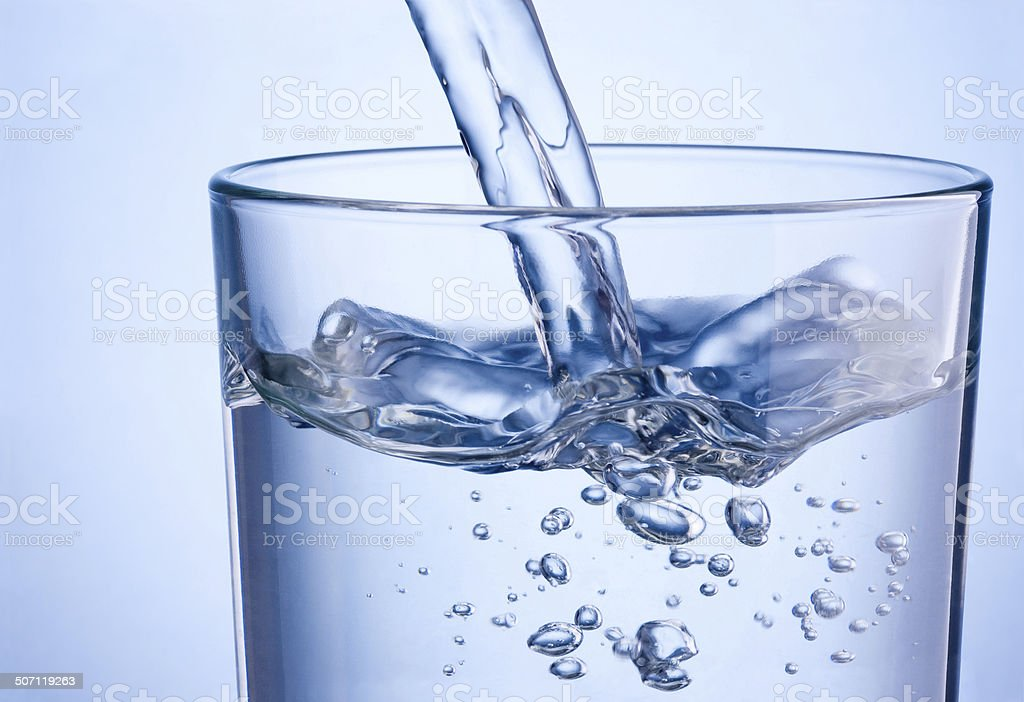 Close up pouring water into glass on a blue background stock photo