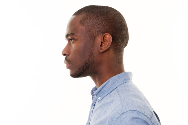 Close up profile of handsome young black man against isolated white background Close up profile portrait of handsome young black man against isolated white background profile view stock pictures, royalty-free photos & images