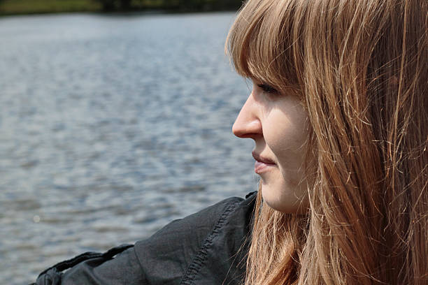 beautiful latvian outdoor girl in profile water background - whiteway latvian outdoor girl stock photos and pictures