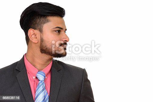 istock Close up profile view of young handsome Indian businessman looking away 668538116