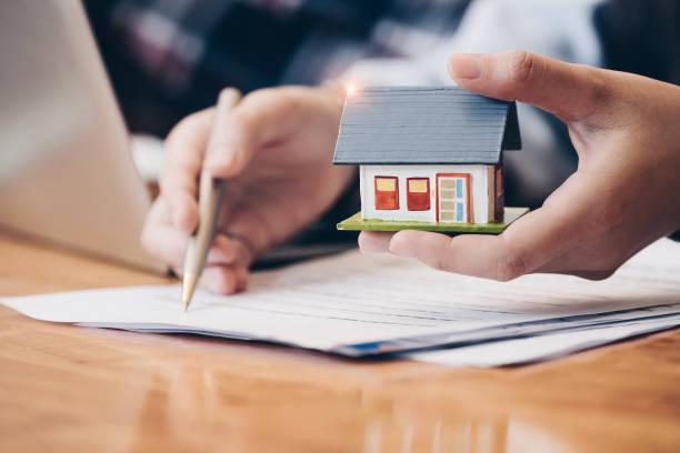 nahe schließen immobilienmakler mit haus modell hand setzen unterzeichnen vertrag, haben einen vertrag, um es zu schützen, die unterzeichnung von bescheidenen vereinbarungen form im amt. konzept immobilien, umzug nach hause oder vermietung von immobilien - eigenheim stock-fotos und bilder