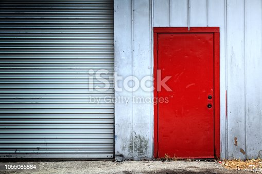 Close up red door and shiny metal garage door detail from old rusty warehouse building