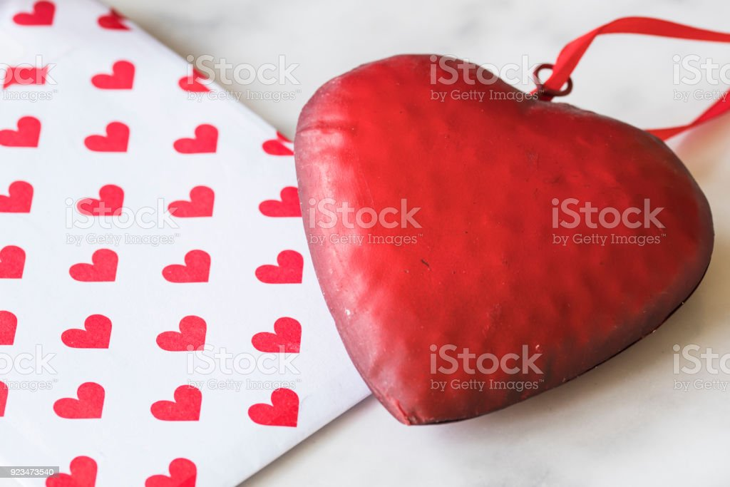 close up red metal heart with ribbon, envelope with pattern, on white marble background stock photo