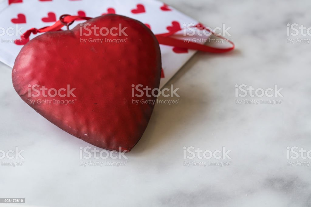 close up red metal valentine heart with ribbon, envelope with pattern, on white marble background, space for text stock photo