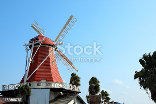 Traditional Netherlands culture of close up red wooden windmill over sunny blue sky