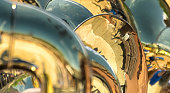 A close up of brass instruments in a marching band. There are multiple reflections of other instruments and unrecognisable band members.
