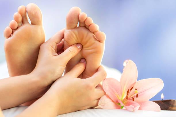Close up reflexology massage on feet. stock photo
