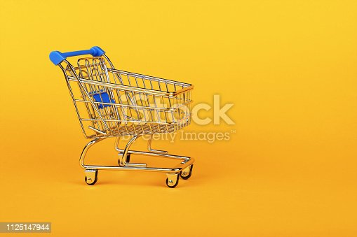 Close up empty toy metal supermarket shopping cart over vivid yellow background with copy space, low angle side view