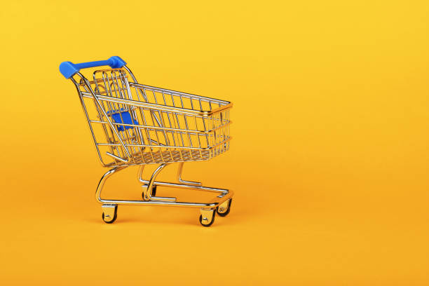 Close up retail shopping cart over yellow Close up empty toy metal supermarket shopping cart over vivid yellow background with copy space, low angle side view cart stock pictures, royalty-free photos & images