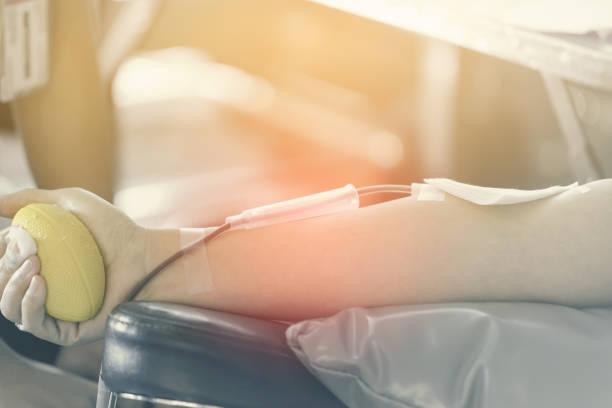 Schließen Sie den rechten Arm des asiatischen Mannes, der Blut empfängt und hält Gummikugel in der Hand. Gesundheit und Nächstenliebe. Transfusion Blutspende. WeltBlutspendetag – Foto
