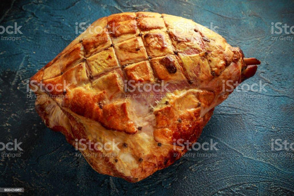 Close up Roasted whole ham on rustick background stock photo