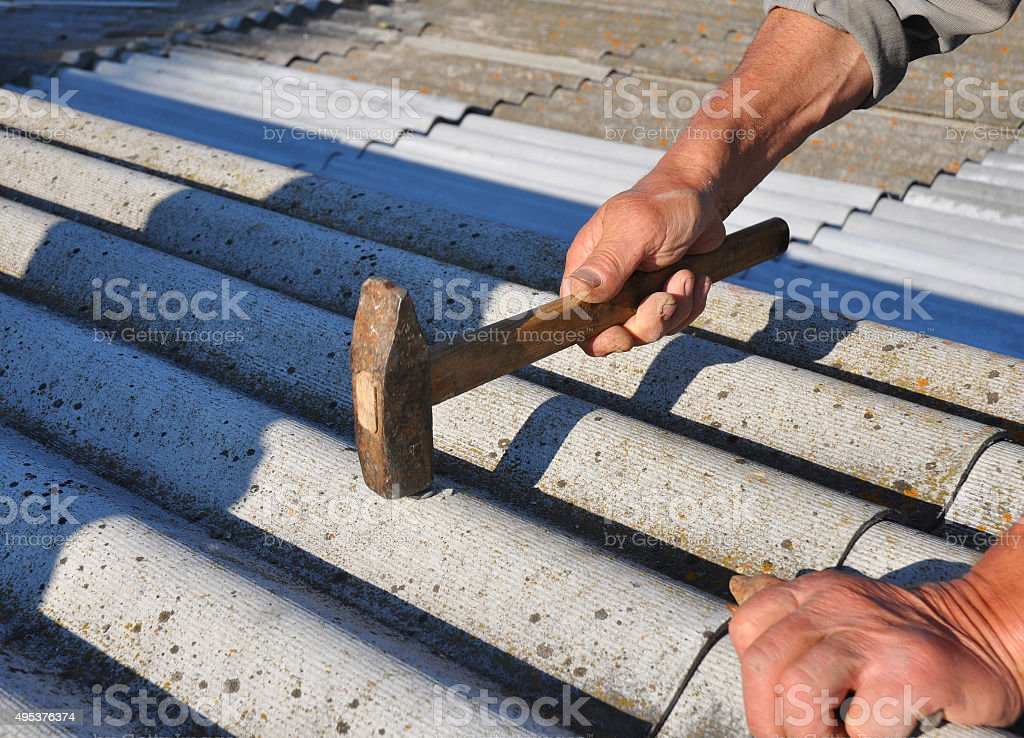 Close up Roofer Hammering Nail in Asbestos Roof Tiles. stock photo
