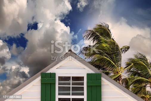 close up rooftop of a wooden house over stormy clouds sky and waving palm tree leaves