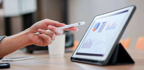 nahaufnahme verkäufer mitarbeiter hand mit stift stift auf tablet-bildschirm zeigen, um unternehmensgewinn monatlich in der tagungsveranstaltung im konferenzraum, geschäftsstrategie-konzept zu zeigen - geschäftsstrategie stock-fotos und bilder