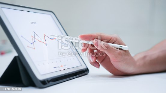 675825950 istock photo close up salesman employee hand using stylus pen to pointing on tablet screen to show statistic graph of company profit monthly in the meeting event at conference room , business strategy concept 1176180149