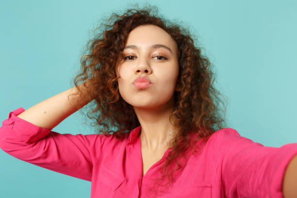 Close up selfie shot of pretty african girl in casual clothes blowing sending air kiss isolated on blue turquoise background in studio. People sincere emotions, lifestyle concept. Mock up copy space. stock photo