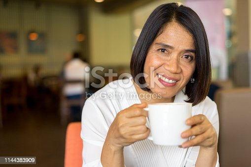 istock close up senior asian woman smiling and holding cappuccino flavor coffee cup inside cafe on weekend , lifestyle mature concept 1144383909