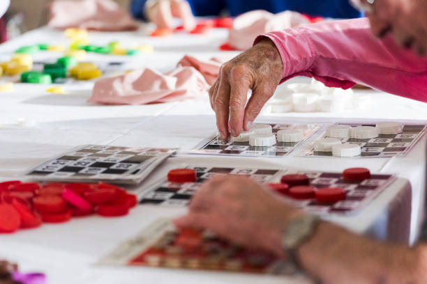 Close up senior man places piece on bingo number card stock photo