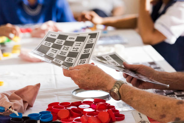 Close up senior mans hands passing out number cards for a game of bingo stock photo