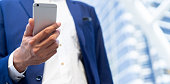 close up senior sales executive businessman hand holding smartphone to checking work or email or investment profit at city building outdoor with copy space background for business technology concept