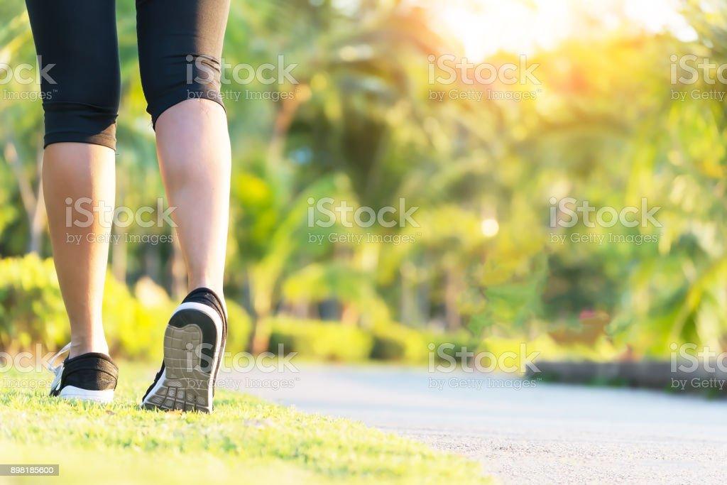 Gros chaussures, jambes. course de vue arrière femme runner sport, fille marche dans le parc. Sport exercice bénéfice. entraînement en plein air. corps de perte de poids fort. Lent à quelques prestations de concept de défi sportif. - Photo