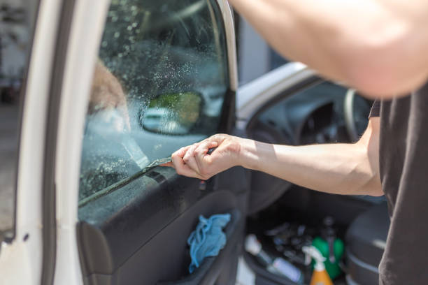 Close up shot hands of man removing old car window film Worker removing old car window glass protective tint foil from side window. detach stock pictures, royalty-free photos & images